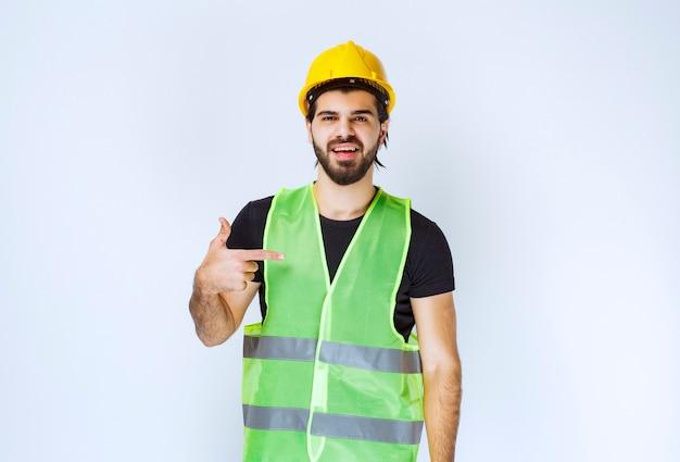 Travailleur en casque jaune pointant sur lui-même.