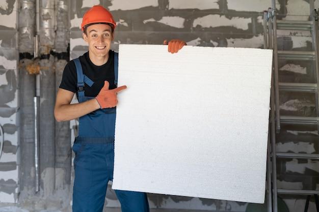 Travailleur avec casque orange près d'un mur de pierres. tenant une grande feuille de polystyrène dans ses mains. pointez votre doigt sur un espace vide pour le texte.