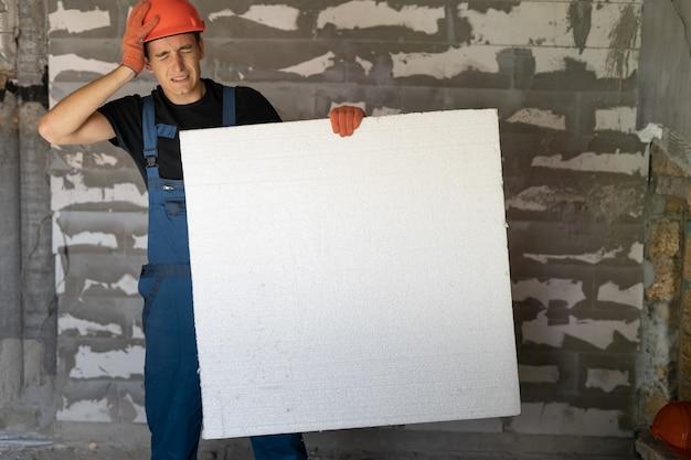 Travailleur avec casque orange près d'un mur de pierres. tenant une grande feuille de polystyrène dans ses mains. tient sa tête avec sa main. espace de copie