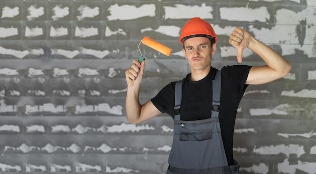 Travailleur avec casque orange près d'un mur de pierres. tenant un rouleau dans ses mains pouce vers le bas