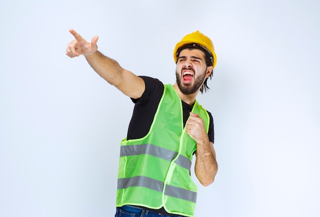 Travailleur en casque pointant sur le côté gauche et montrant son poing.