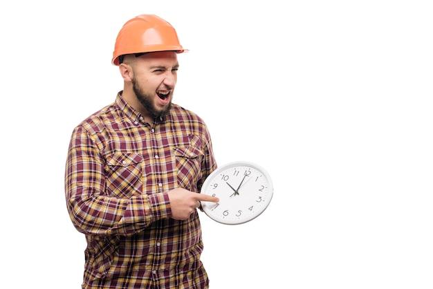 Travailleur en casque de protection tenant un réveil sur blanc. temps de travailler. temps de construction du bâtiment