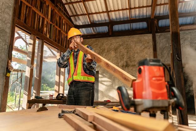 Travailleur de charpentier professionnel d'âge moyen attrayant et travailleur à la recherche et au choix du bois sur une table en bois sur le chantier de construction.