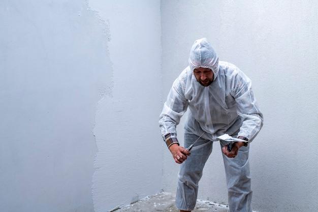 Travailleur en combinaison de protection blanche enduit le mur