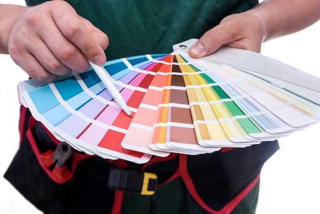Travailleur en combinaison tenant un échantillon de couleur isolé sur blanc