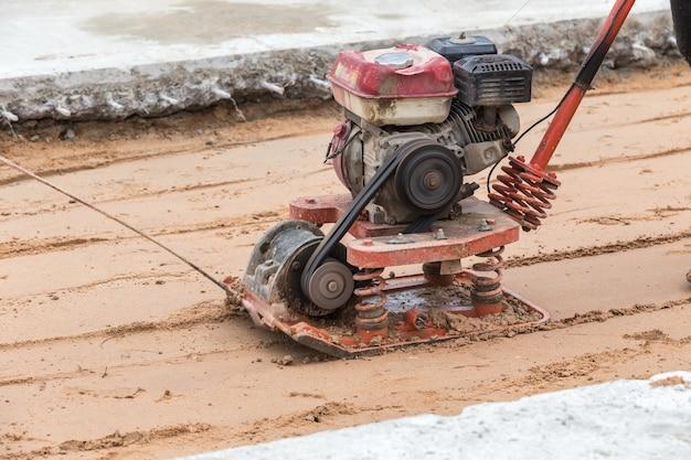 Travailleur avec des compacteurs de sol dans le chantier de construction