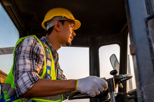 Travailleur de conduite tracteur à roues lourdes, chargeuse sur pneus excavatrice avec pelle rétrocaveuse sable fonctionne en chantier.