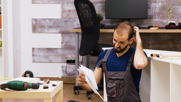 Travailleur confus se frottant la tête en lisant des instructions pour de nouveaux meubles. perceuse électrique sur table basse.