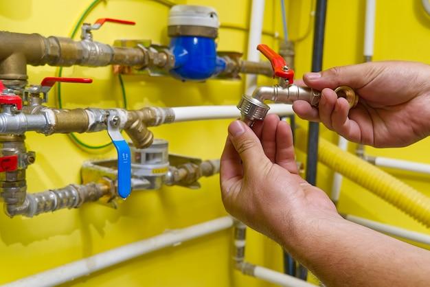 Le travailleur connecte un raccord rapide pour l'eau du jardin.