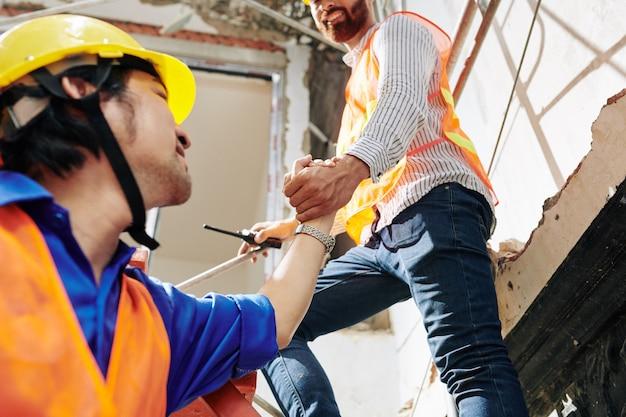 Travailleur de la construction aidant un collègue