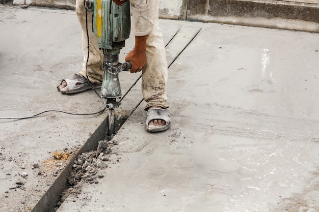 Travailleur de la construction à l'aide de marteau-piqueur de surface en béton