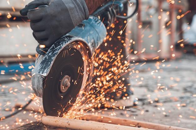 Travailleur de la construction à l'aide de meuleuse d'angle de coupe de métal sur le chantier.