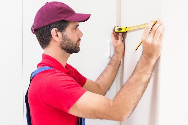 Travailleur de la construction à l'aide d'un ruban à mesurer