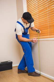 Travailleur de la construction à l'aide de ruban à mesurer