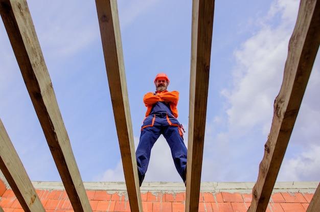 Travailleur de la construction sur le chantier de construction charpentier constructeur travaillant sur la structure du toit sur