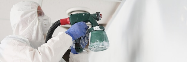 Travailleur de la construction en combinaison de protection et mur de peinture de respirateur avec pistolet de pulvérisation