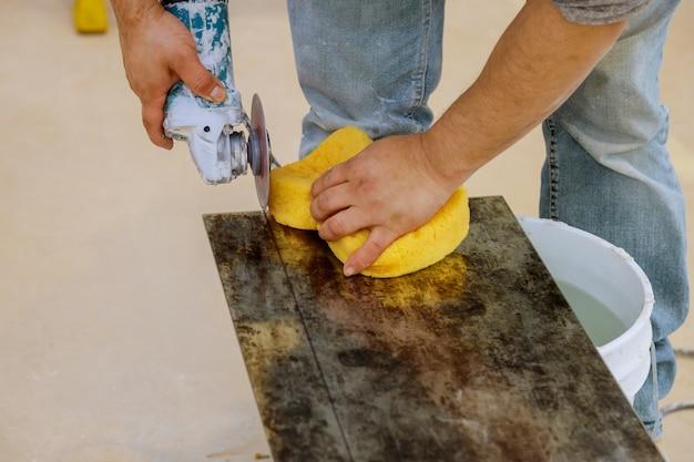 Un travailleur de la construction coupant une tuile à l'aide d'un broyeur
