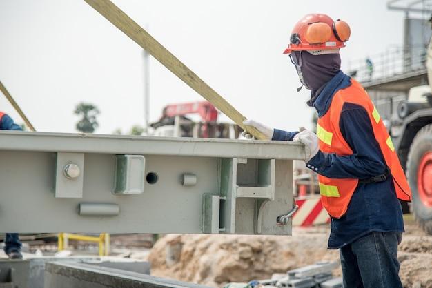 Travailleur de la construction dans la structure de l'échelle de camion de stalle dans l'uniforme de sécurité de chantier de construction