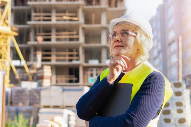 Un travailleur de la construction féminin dans un gilet et un casque sur le fond d'un nouveau bâtiment
