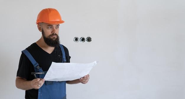 Travailleur de la construction masculin brutal avec une barbe, vêtu d'un uniforme de travail bleu et d'un casque orange. contient une feuille de papier avec des dessins. espace de copie.