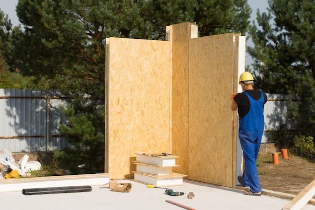 Travailleur de la construction masculin construisant un mur de maison immobilière seul.