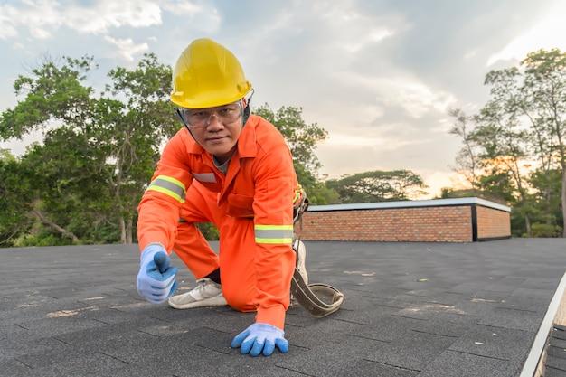 Travailleur de la construction mettant la toiture en asphalte (bardeaux) avec pistolet à clous sur un grand immeuble à appartements