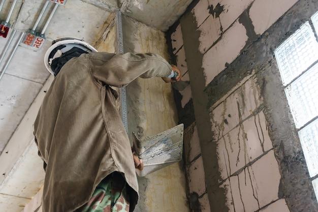 Travailleur de la construction avec des outils de plâtrage mural