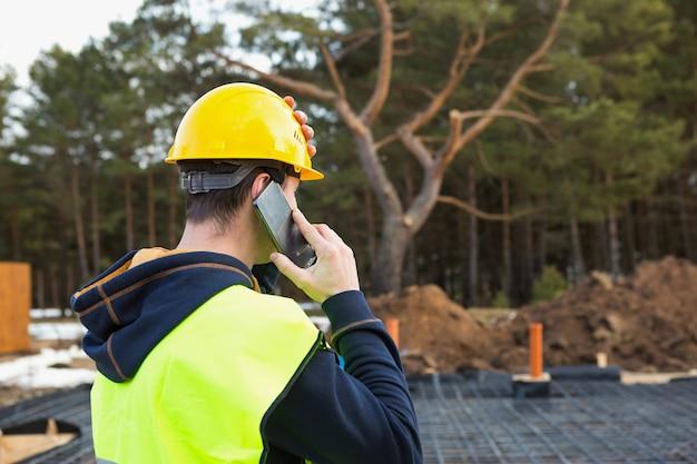 Travailleur de la construction parle sur un smartphone dans un casque jaune et un gilet de protection