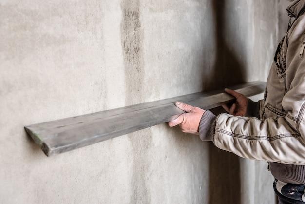 Travailleur de la construction plâtrant un mur avec niveleur