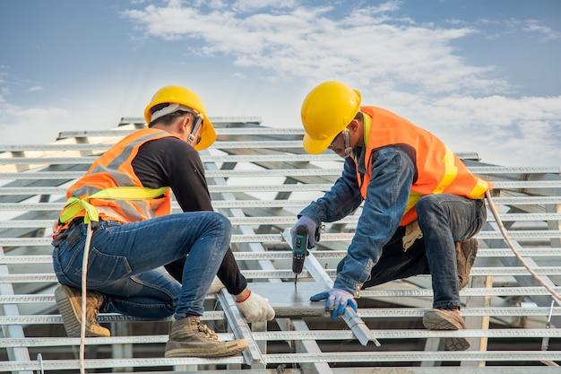 Travailleur de la construction portant une ceinture de sécurité lors de l'installation de tuiles de toit en béton sur le nouveau toit.