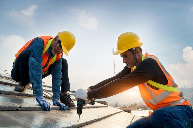 Travailleur de la construction portant une ceinture de sécurité pendant le travail sur la structure du toit du bâtiment sur le chantier.