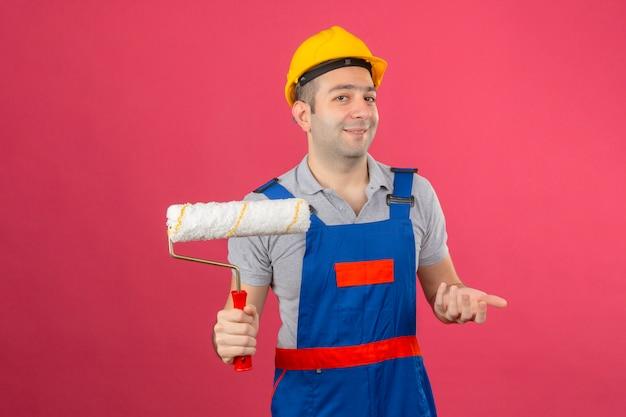 Travailleur de la construction portant un uniforme et un casque de sécurité faisant un geste confus avec la main et l'expression comme posant une question tenant un rouleau à peinture isolé sur rose