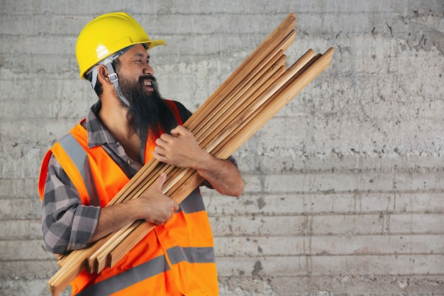 Un travailleur de la construction porte des planches de bois très fort sur le chantier.