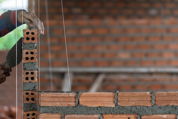 Travailleur de la construction professionnelle de gros plan posant des briques sur le nouveau site industriel