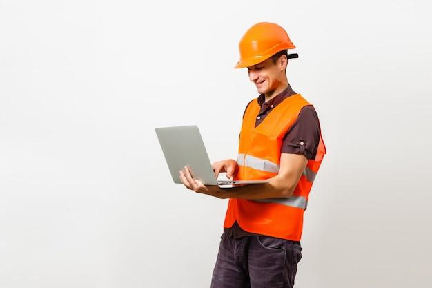 Travailleur de la construction sympathique tenant un ordinateur portable avec un espace noir pour votre message. isolé sur blanc.