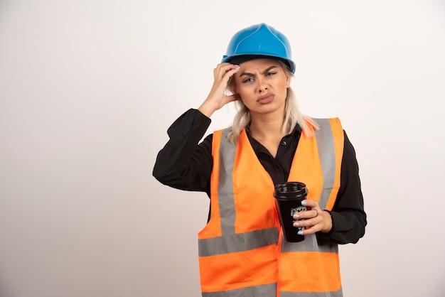 Travailleur de la construction avec une tasse de thé ayant mal à la tête. photo de haute qualité