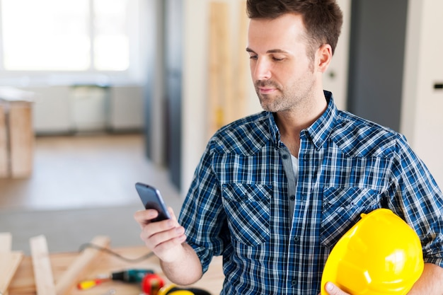 Travailleur de la construction avec téléphone mobile contemporain