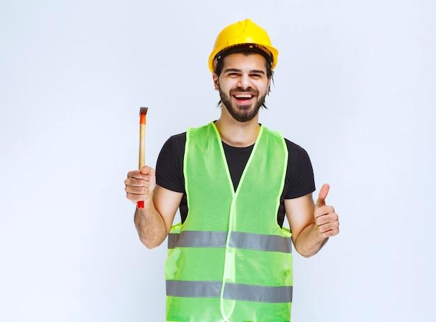 Travailleur de la construction tenant un marteau à griffes et montrant un signe de plaisir.