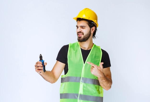 Travailleur de la construction tenant une pince bleue.