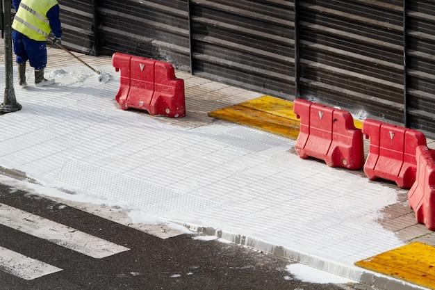 Travailleur de la construction travaillant avec du béton blanc sur un trottoir en réparation. concept d'entretien de la ville