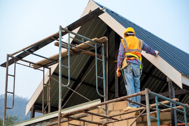 Travailleur de la construction travaille sur des échafaudages et porte un harnais de sécurité pour la sécurité de travail sur le chantier de construction.