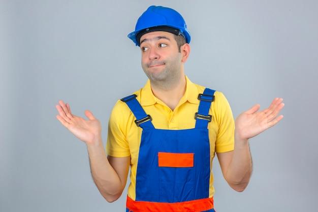 Travailleur de la construction en uniforme et casque de sécurité bleu désemparé et expression confuse avec les bras et les mains levées isolated on white