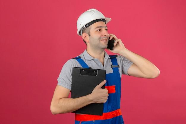 Travailleur de la construction en uniforme et casque de sécurité s'exprimant par téléphone mobile tenant le presse-papiers positif à la recherche isolé sur rose