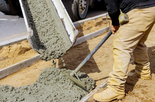 Travailleur de la construction verser le ciment pour trottoir dans les travaux de béton avec camion malaxeur avec brouette