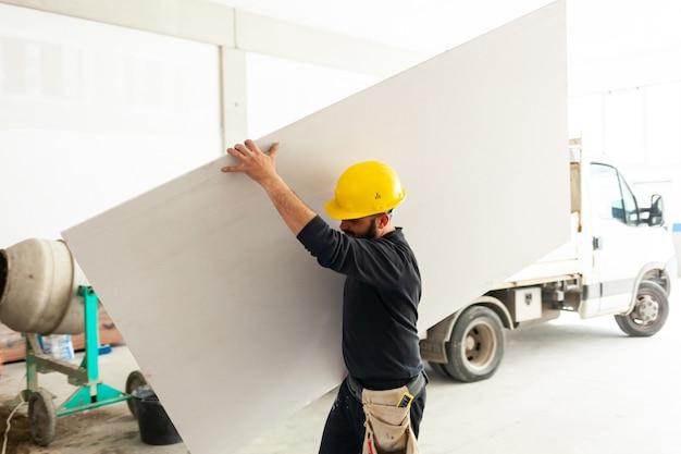 Travailleur construit un mur de plaques de plâtre