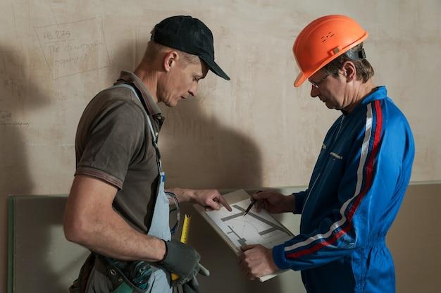 Un travailleur et un contremaître discutent du plafond en plaques de plâtre