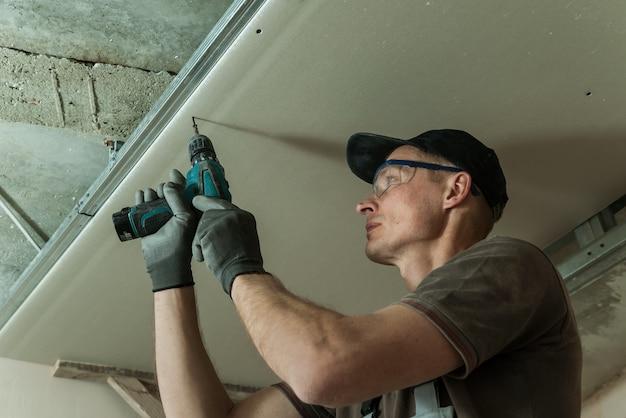 Un travailleur corrige la cloison sèche