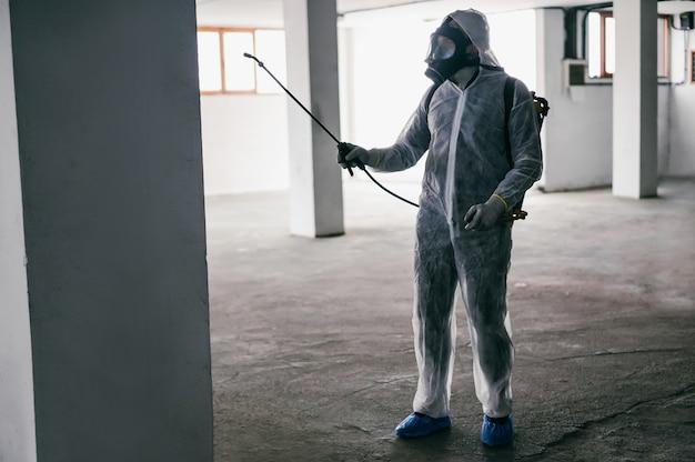 Travailleur en costume de matières dangereuses portant un masque de protection lors de la désinfection à l'intérieur du bâtiment du parc de la ville