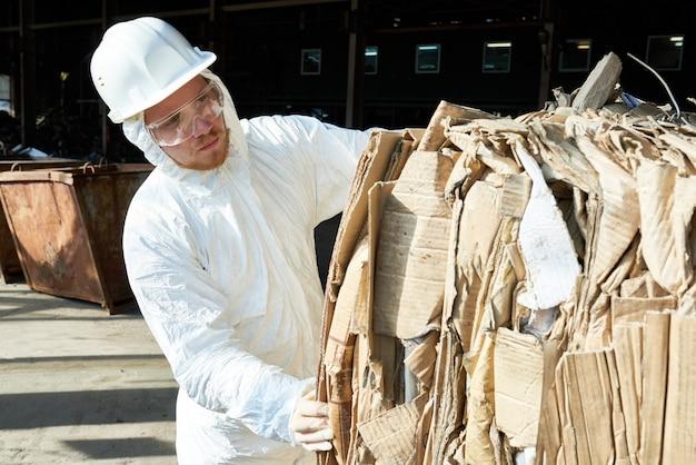 Travailleur en costume de matières dangereuses triant le carton à l'usine de recyclage