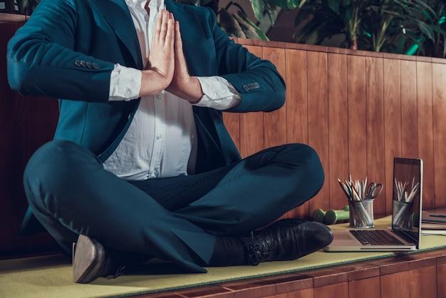 Travailleur en costume méditant sur un banc dans le bureau.